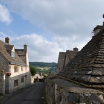 a photograph of stone cottages in the Cotswolds, England with a view overlooking the valley beyond