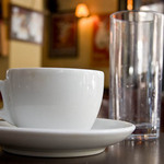 a photograph of a coffee cup and empty glass on the table in a cafe