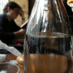a photograph of the interior of a cafe in Paris with carafe of wine on a table
