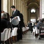 a photograph of tables with a waiter serving in a cafe in Paris