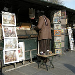 a photograph of a Paris bookseller standing reading by his bookstall by the river Seine