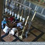 people prostrating themselves in the Church of the Holy Sepulchre in Jerusalem