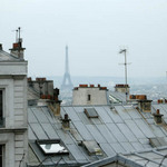 A photograph of a view over Paris rooftops with a view of the Eiffel Tower