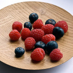photo of raspberries and blueberries on a wooden plate