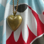 photo of a gold colored heart-shaped pendant against blue, white, red, and black patterned material