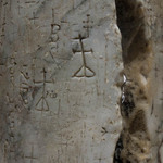 photo of carved old religious graffiti on a marble column in the Church of the Holy Sepulchre in Jerusalem