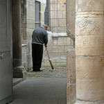 photo of a man sweeping with a broom in a courtyard of an old stone-built church in Paris