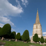 photo of a church spire and trees in a churchyard in the Cotswolds in England