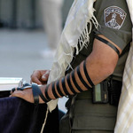 photo of Israeli Defence Force soldier with tefillin, phylacteries, praying at the Western Wall in Jerusalem