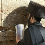 photo of a man in a shtreimel (fur hat) praying at the Western Wall in Jerusalem