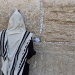 photo of a man with a tallit (prayer shawl) over his head praying against the Western Wall in Jerusalem