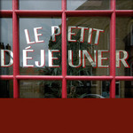 photo of the window of a restaurant with the words 'Le Petit Dejeuner' in red and gold lettering and a quotation about eating by Will Rogers