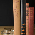 photo of four books showing their spines, and an inkwell